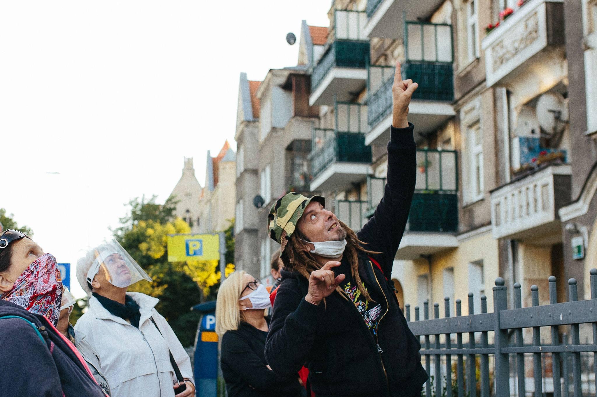 Mężczyzna pokazujący stojącym ludziom palcem coś pond ich głowami
