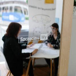 """Dwie osoby siedzą przy stoliku i rozmawiają. Ich podobizny odbite są w lustrze, na którym widnieje napis: """"Szczecin to Wy""""."""