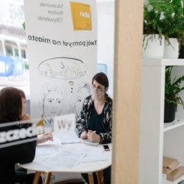 Dwie kobiety siedzą przy stoliku i rozmawiają, widzimy to w odbiciu w lustrze, na którym widnieje napis: Szczecin to Wy.