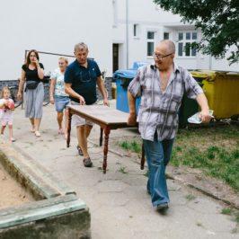 Ludzie w różnym wieku niosą na podwórku stół