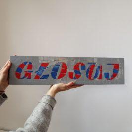 """Ręce trzymające małą mozaikę z napisem: """"GŁOSUJ"""""""